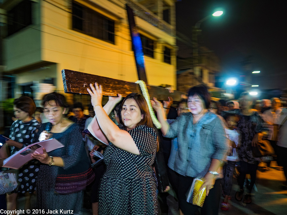 25 MARCH 2016 - BANGKOK, THAILAND:  Parishioners carry a cross past the church during Good Friday observances at Santa Cruz Church in Bangkok. Santa Cruz was one of the first Catholic churches established in Bangkok. It was built in the late 1700s by Portuguese soldiers allied with King Taksin the Great in his battles against the Burmese who invaded Thailand (then Siam). There are about 300,000 Catholics in Thailand, in 10 dioceses with 436 parishes. Good Friday marks the day Jesus Christ was crucified by the Romans and is one of the most important days in Catholicism and Christianity.     PHOTO BY JACK KURTZ