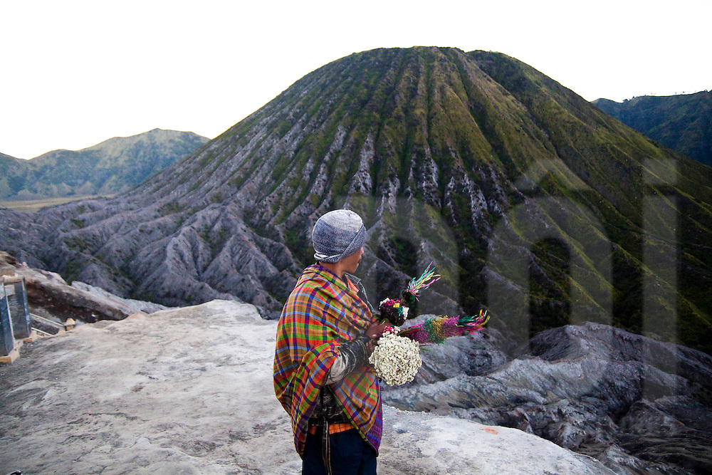 A vendor selling flower offerings to be thrown into the crater waits for customers at its edge on Mount Bromo in East Java, Indonesia, Southeast Asia