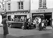 15/05/1959<br /> 05/15/1959<br /> 15 May 1959<br /> Gael Linn Competition at Listowel, Co. Kerry. Picture shows dancing in the streets outside J.P. Kennelly's and Kerin's shop. Fiddler is possibly Sean Maguire.