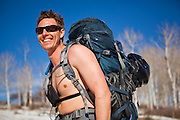 Peter Richardson barechested carrying a large backpack on a backcountry ski trip in the San Juan Mountains, Colorado.