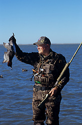 Stock photo of an older man standing in the water and holding a duck that he killed
