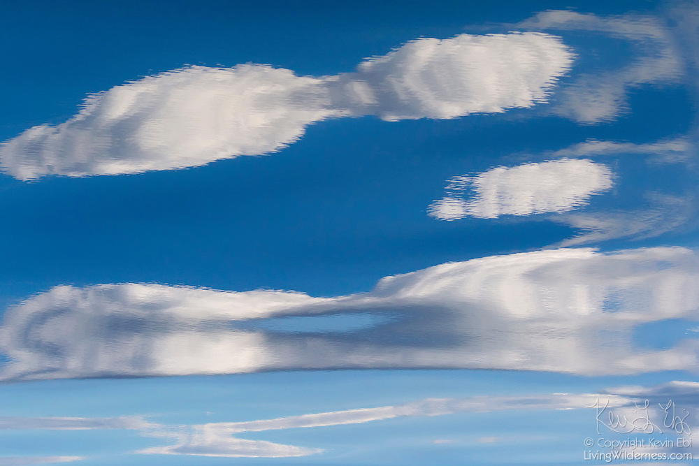 Several cumulus humilis clouds are reflected in the rippled waters of the Rosario Strait off Orcas Island, Washington.