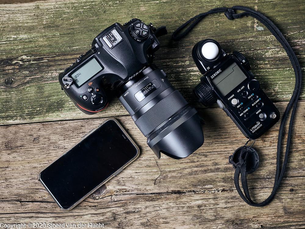Photo camera with light meter and iPhone 11 pro on wooden table. | Fotocamera met lichtmeter en iPhone 11 pro op houten tafel.