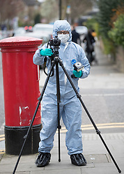© Licensed to London News Pictures.19/03/2017.London, UK. A police forensics officer photographs the area where a hammer was found in a builder's bag of sand round the corner from Wilberforce Road where one baby has been found dead and another seriously injured in Finsbury Park. Police have named  Bidhya Sagar Das who lives at the property and is wanted in connection with the death.  Photo credit: Peter Macdiarmid/LNP
