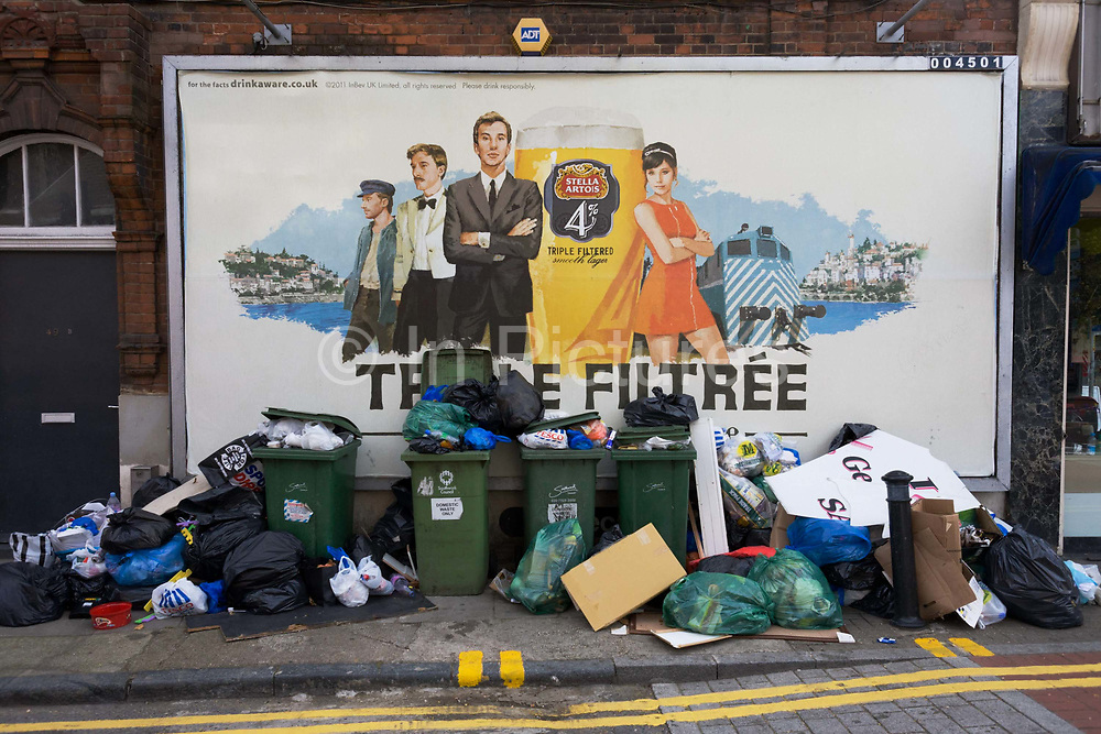 A landscape in a London street of street rubbish (garbage) left below a Stella Artois alcohol billboard. A chic man and woman from the sixties (1960s) stand with all the confidence of the style of a previous era with a landscape of the Mediterranean with its azure blue waters. But the reality of 2011 south London is a far removed from the utopia on the ad. Fly tipping has added to the already untidy pavement (sidewalk) also blocking pedestrian access. Wheelie bins and plastic bags of rubbish attract vermin and poor hygiene and the council workmen will soon appear to once again clear away the mess - before another pile appears.