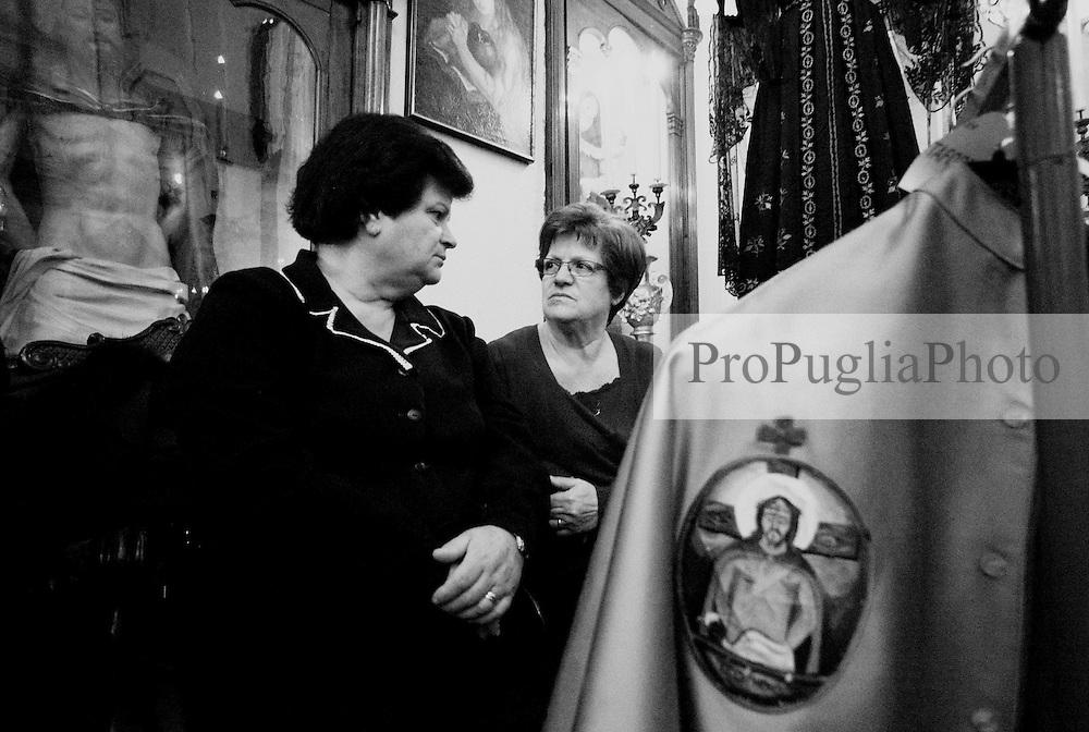 Reportage sulla processione del venerdi santo a Gallipoli...due donne attendono di vestire i confratelli sull'altare della chiesa.