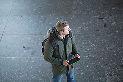 High angle view of a young man holding a digital tablet and looking away, Freiburg im Breisgau, Baden-Wuerttemberg, Germany