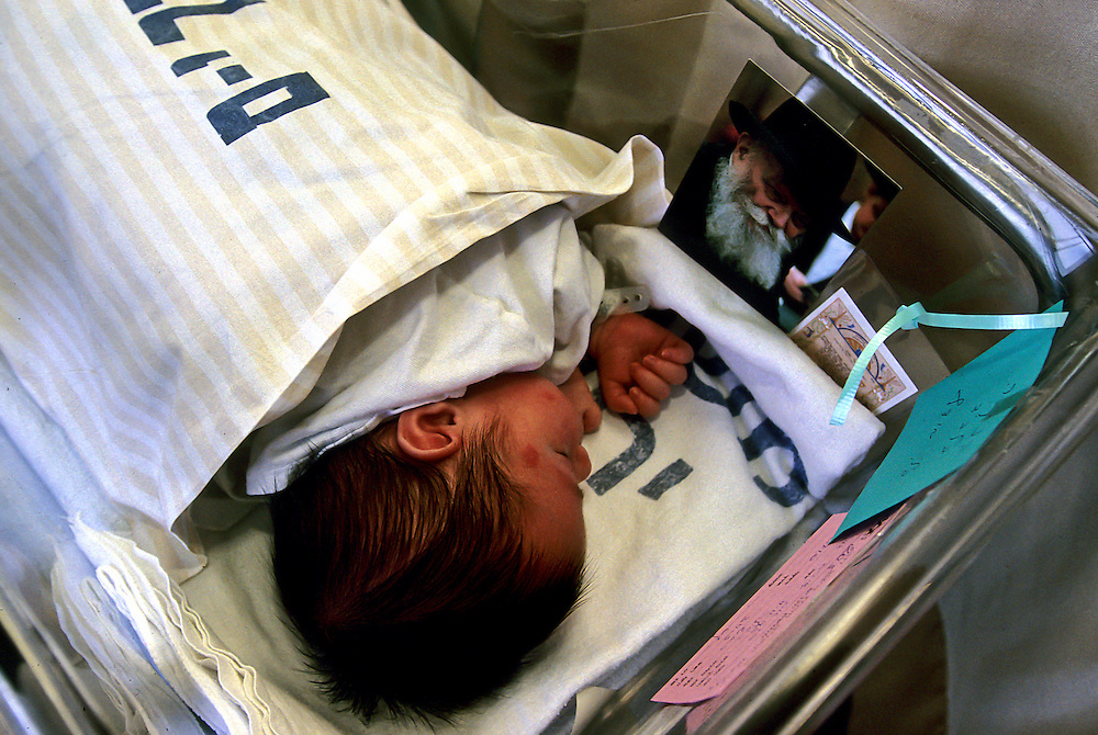 A newly born Jewish baby with the picture of a Rabbi in his bassinet.