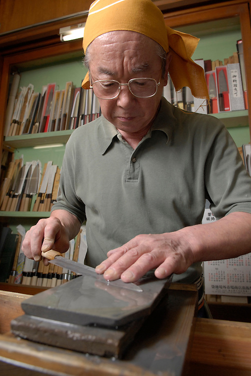 3rd generation knife shop owner Azuma Masahisa sharpening a cooking knife in his shop.