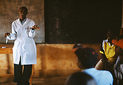 Health educator Theogene Niyongana gives a lecture on HIV and AIDS to a group of people waiting to be tested for the virus at Kibayi Health Centre. By addressing their status, sufferers learn how to increase their life expectancy. Kibileze, Rwanda.