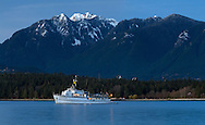 Crown, Goat and Grouse Mountains with some fresh, spring snowfall behind Stanley Park and the fishing charter yacht M.V. Edgewater Fortune in English Bay.  Photographed from Kitsilano Beach Park in vancouver, British Columbia, Canada.