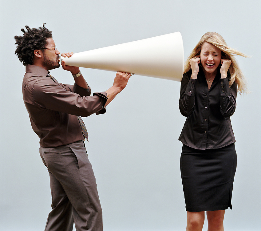 30 something man yelling into megaphone pointed at woman, woman plugging ears