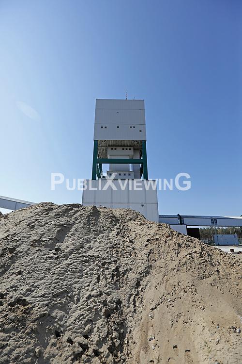 Der Förderturm des Erkundungsbergwerks in Gorleben hinter einem großen Sandhaufen, verursacht durch den Abriss der Betonmauer rund um das Bergwerk.<br /> <br /> Ort: Gorleben<br /> Copyright: Andreas Conradt<br /> Quelle: PubliXviewinG