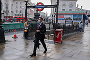 After a rain shower in central London - the six-month point of the Coronaviruus pandemic lockdown - a businessman wearing a suit and face covering (over his mouth but not nose), strides through Piccadilly Circus carrying a brolly, on 24th September, in London, England. New restrictions are being re-introduced by the government after a sudden climb in the Covid infection rate, a predicted 'second spike'. And after being encouraged back to the office to help local economies, workers are again being advised to work from home if possible.