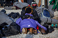 MYTILINI, GREECE - FEBRUARY 08: A refugee sleeps holding her daughters's coat while waiting for registration after his arrival at the Moria refugee camp on February 08, 2015 in Mytilini, Greece. Refugees are transferred to the Moria refugee camp after their arrival at the beaches of Lesvos from the Turkish coast. After travelling for more than two hours crossing the Aegean sea, refugees are picked up by buses run by UNHCR and transferred to the Moria refugee camp where they have to register their names. As thousands of refugees arrive everyday in Lesvos, queues for registration can take up to two days. In the camp several international organisations provide assistance to the refugees as food, medical assistance, blankets and clothes among other items and services. Photo: © Omar Havana. All Rights Are Reserved