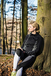 Young female jogger having a break while listening music on smart phone in forest