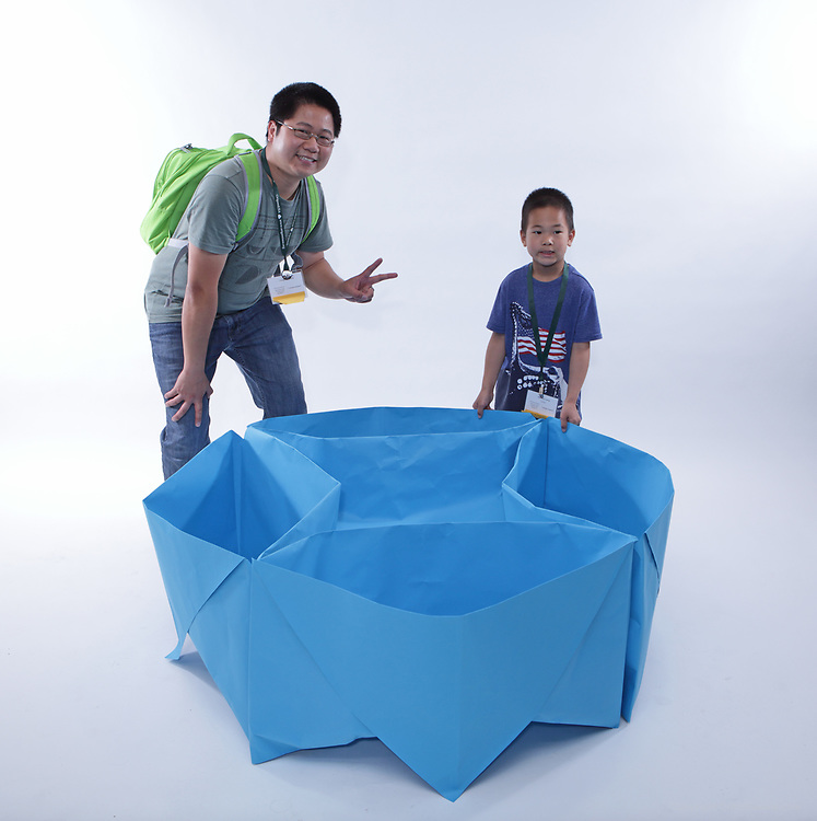 New York, NY, USA - June 24, 2018: Scenes from the Big Folding event at the annual OrigamiUSA Convention. Featured in this picture left to right: Yangwen Liang (first timer), CA, Nathan Liang (first timer), CA. Model: Lazy susan.