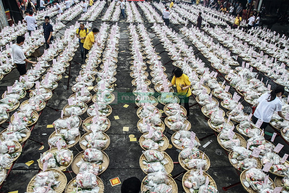 September 5, 2017 - Medan, North Sumatra, Indonesia - An Ethnic-Chinese Indonesian arranges offerings for her ancestors' souls during the ''hungry ghost'' festival in Medan, Indonesia. During the month-long festival, Chinese people make offerings of food, hell money and paper-made models of items such as televisions, servants and cars to be burnt to appease the wandering spirits as it is believed that the gates of hell are opened during the month and their dead ancestors return to visit their relatives. (Credit Image: © Ivan Damanik via ZUMA Wire)