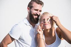 Young man smiling with his playful girlfriend making moustache with hair, Bavaria, Germany