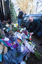 Highgate, London, December 26th 2016. Fans gather outside the London home of pop icon George Michael who died on Christmas day. PICTURED: A man places his flowers among the tributes outside the gate.