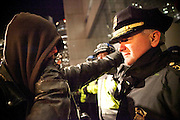 A protester and a police officer stare hard each other as Occupy Boston members protest about the raid which occured two days ago  in Boston, Massachusetts, December 12, 2011.