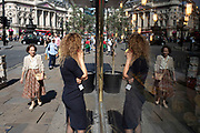 Woman on her mobile phone and passers by create a symmetrical reflection in a shop window along Piccadilly in London, United Kingdom.