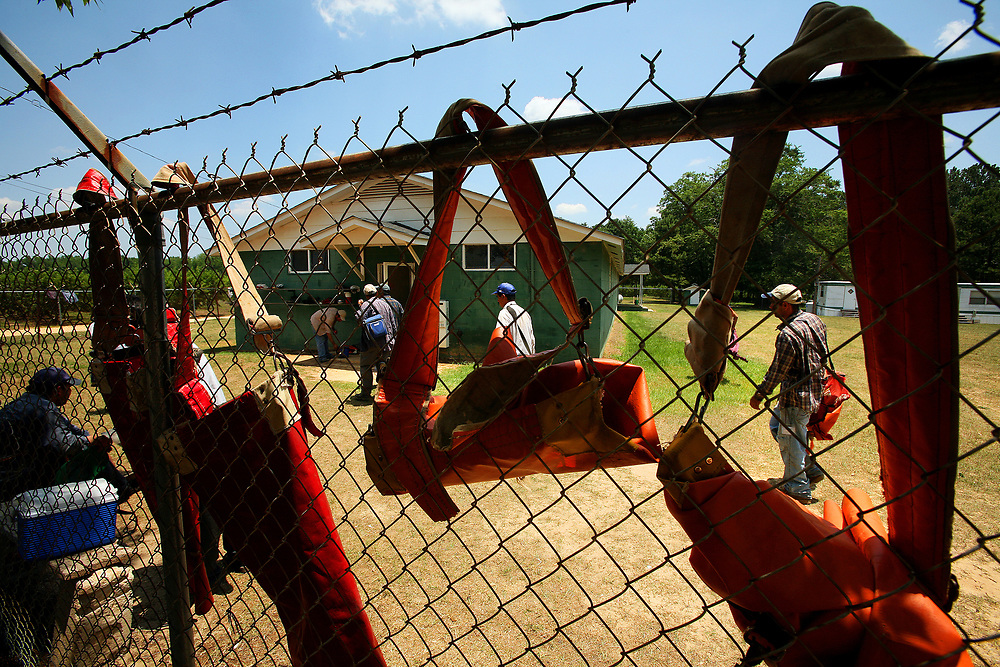 Empty peach sacks hang from a fence as migrant workers make their way into their community home after a long day in the fields.
