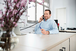 Manager in office using landline telephone