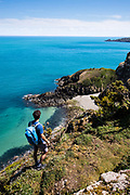 Man out walking and exploring the cliffs on the north coast and looking down towards the view of Vicard Harbour, a pebbly bay hidden in amongst the cliffs and surrounded by calm seas.