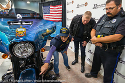 Captain Debra Bodenstedt of Yankton, USN Ret and chairwoman of the commissioning committee shows SD Highway Patrol features of the 2018 Harley-Davidson Street Glide donated by the Motor Company and customized by J and L Harley-Davidson to commemorate the christening of the USS South Dakota submarine. Sioux Falls, SD. USA. Monday October 9, 2017. Photography ©2017 Michael Lichter.