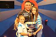 Gerwyn Price wins and holds aloft The Eric Bristow Trophy with his two daughters during the Grand Slam of Darts, at Aldersley Leisure Village, Wolverhampton, United Kingdom on 17 November 2019.