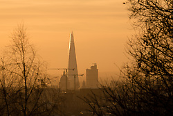 © Licensed to London News Pictures. 28/01/2015. London, UK. Warm orange sunrise over the London Shard and St Paul's Cathedral from Hampstead Heath during cold weather this morning. Photo credit : Vickie Flores/LNP