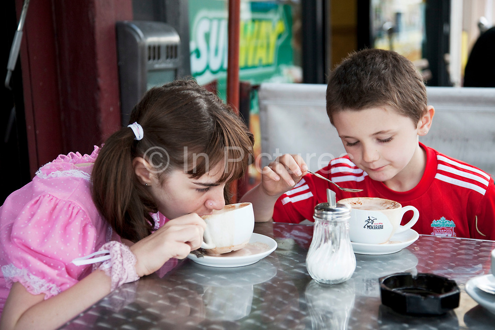 Georgia (11, wearing a pink Lolita dress) and her brother Kiefer (8, wearing a red Liverpool Football Club kit) having a treat of hot chocolate whilst spending a day out together in Camden Town, North London. Louise (their mother) is on various benefits to help support her family income, and housing, although recent government changes to benefits may affect her family drastically, possibly meaning they may have to move out of London. Louise Ryan was born on the Wirral peninsula in 1970.  She moved to London with her family in 1980.  Having lived in both Manchester and Ireland, she now lives permanently in North London with her husband and two children. Through the years Louise has battled to recover from a serious motorcycle accident in 1992 and has recently been diagnosed with Bipolar Affective Disorder. (Photo by Mike Kemp/For The Washington Post)