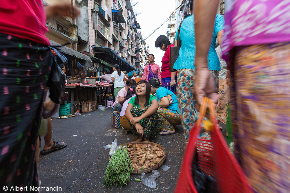 Young woman street vendor in middle of very busy street market