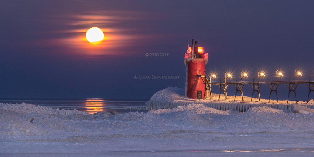 A wintry scene with the full moon beginning to set on Lake Michigan in view of the South Beach lighthouse in South Haven.