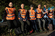 Insulate Britain climate activists lean on a safety barrier after being detained by Surrey Police following their blocking of the clockwise carriageway of the M25 between Junctions 9 and 10 as part of a campaign intended to push the UK government to make significant legislative change to start lowering emissions on 21st September 2021 in Ockham, United Kingdom. Both carriageways were briefly blocked before being cleared by Surrey Police. The activists are demanding that the government immediately promises both to fully fund and ensure the insulation of all social housing in Britain by 2025 and to produce within four months a legally binding national plan to fully fund and ensure the full low-energy and low-carbon whole-house retrofit, with no externalised costs, of all homes in Britain by 2030.