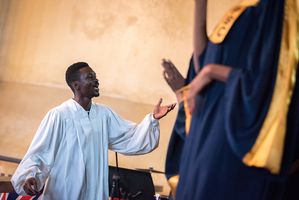 3 November 2019, Monrovia, Liberia: Choir director in action during Sunday service at the Providence Baptist Church, also known as 'the cornerstone of the nation', as it was in the Providence Baptist Church that Liberia's declaration of independence was signed. While this Sunday service is taking place in a larger worship space finalized in 1976, the old chapel remains in place adjacent to the new one, and is still in use.