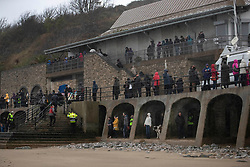 © Licensed to London News Pictures. 11/11/2018. Folkestone, UK. People watch as artists struggle to create a sand portrait of First World War poet Wilfred Owen on the beach at Folkestone, Kent as the weather turns wet and windy at an Armistice Centenary event entitled 'Pages of the Sea'. Portraits are being created by communities on 32 beaches around the UK to say goodbye and thank you, to the millions of men and women who left these shores during the war, many never to return. Lieutenant Wilfred Edward Salter Owen, MC died on 4th November 1918 only days before the Armistice. One of Britain's most celebrated war poets - his short career was directly inspired by the conflict – he composed nearly all his works from August 1917 to September 1918, many published posthumously. Photo credit: Peter Macdiarmid/LNP