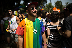 """© Licensed to London News Pictures . 03/06/2016 . Tel Aviv , Israel . A man wearing a large Star of David necklace and a rainbow t-shirt . Over 100,000 people attend the gay pride parade in Tel Aviv , reported to be the largest such event in the Middle East and Asia . The Israeli government has been accused of using the event as """" pinkwashing """" , marketing the event in order to deflect accusations of poor human rights behaviour . Photo credit: Joel Goodman/LNP"""