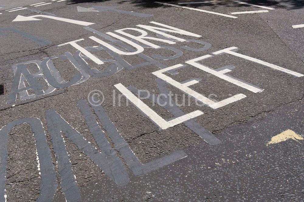 An urban landscape of road markings and the ghosts of previous versions, of the words Turn Left, are seen from an elevated angle, in the road at Aldwych, on 23rd June 2021, in Westminster, London, England.