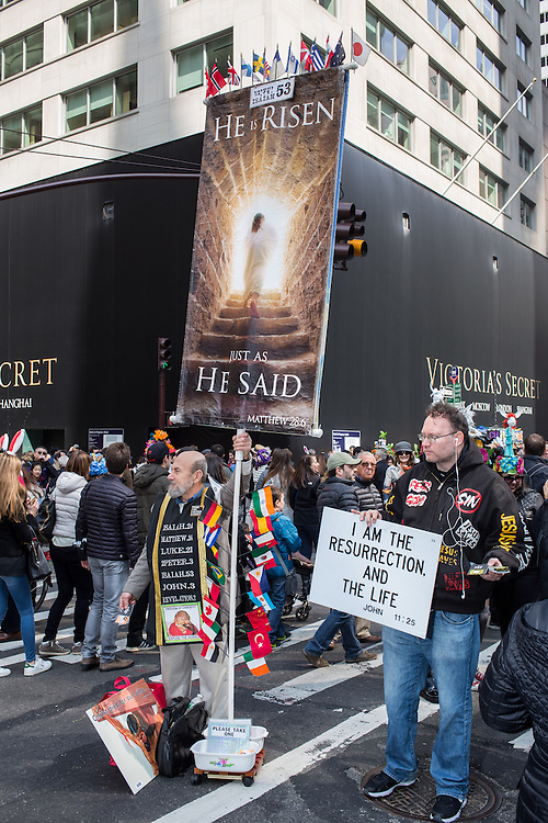 New York, NY, USA-27 March 2016. Two religious proselytizers with signs and a banner try to attract attention on Fifth Avenue in the middle of the annual Easter Bonnet Parade and Festival.