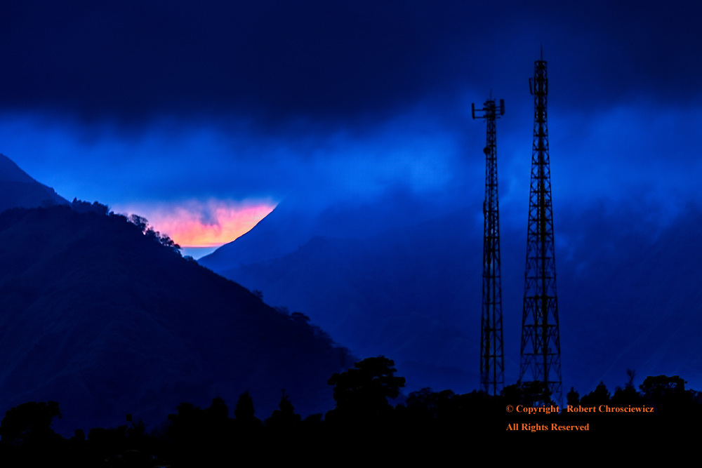 Blue Sunrise: Morning finds a mountainous valley shrouded in layers blue, as heavy clouds and mist engulf two telecommunication towers standing before a distant sunrise, Mentagi, Lombok Indonesia.