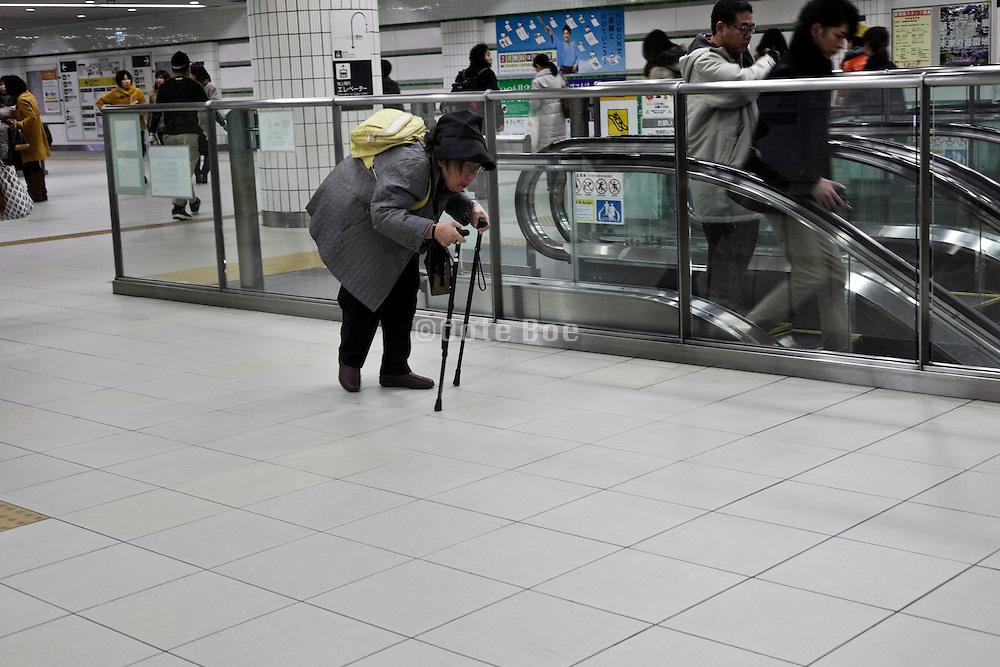 senior woman walking with the help of two walking sticks in train station Yokohama Japan