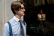 A young man waering braces walks past the luxury shop window of Louis Vuitton featuring their exclusive range of bags with the face of Leonardo da Vinci's Mona Lisa - a collaboration with the artist Jeff Koons and part of work entitled The Masters Collection, on 5th July 2017, on New Bond Street, in London England.