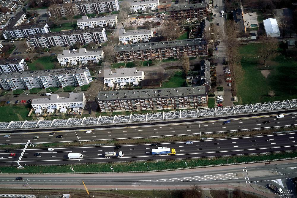Nederland, Zuid-Holland, Dordrecht, 08-03-2002; de zeer verkeersintensieve autosnelweg A16 (Rotterdam -Breda) loopt direct langs de woonwijk ' Wielwijk'; om geluidsoverlast tegen te gaan is een enorm, half gebogen, geluidsscherm gebouwd,  geluidswal met gebogen betonnen spanten en glazen dak; de jaren zestig woonwijk wordt gedeeltelijk gesloopt / gerenoveerd; milieu verkeer en vervoer volksgezondheid .stadsvernieuwing flats;<br /> luchtfoto (toeslag), aerial photo (additional fee)<br /> foto /photo Siebe Swart