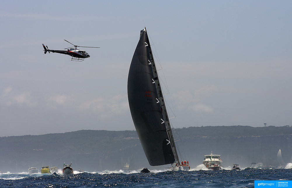 Maxi Wild Oats XI navigates through the flotilla of spectator craft and media helicopters as the fleet heads down the Eastern coastline of Australia after the start of the 64th Rolex Sydney to Hobart Yacht Race 2008 which began in the waters of Sydney Harbor. Exactly 100 yacht's entered in this years race with spectators on the Sydney Harbor foreshore estimated to have reached over 500,000 people on December 26, 2008. Maxi Wild Oats XI skippered by Mark Richards was looking to make history with a record fourth consecutive line honors victory.
