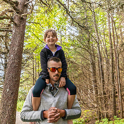 A man walks on a trail at Quoddy Head State Park in Lubec, Maine, while carrying his daughter on his shoulders.
