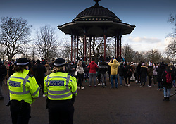 © Licensed to London News Pictures. 13/03/2021. London, UK. Police look on as people gather during an unofficial vigil at the bandstand on Clapham Common for murder victim Sarah Everard. Metropolitan Police officer Wayne Couzens has been charged with the kidnap and murder of Sarah Everard, who went missing as she walked across Clapham Common in south London. The 33-year-old's body was found in Kent just over a week later. Photo credit: Peter Macdiarmid/LNP