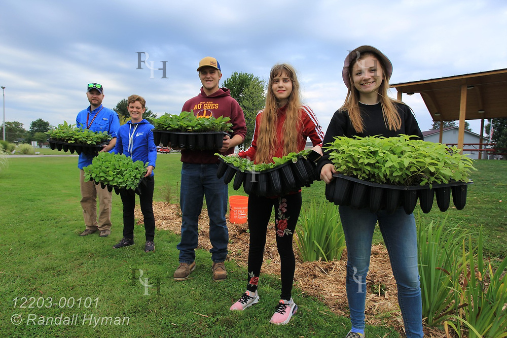 High school environmental sciences students pose with teacher Luke Freeman and Huron Pines community program director Abby Ertel before planting wildflowers in bioswale of rain garden at River Side Park in Au Gres, Michigan.