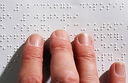 Close up of person with visual impairment reading Braille,
